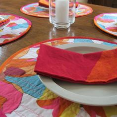 """Bring the summery colors of a beach ball to your table setting with this fun set of round Marimekko placemats! The abstract """"Palma"""" print captures the beauty of orchids in red, orange, turquoise blue, pink and yellow. The other side of the placemat features """"Joiku"""" with the soft look of a watercolor painting in red, orange and fuchia. You'll have twice the fun – the placemats are reversible. Mix and match the flower print with the graphic print."""