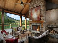 """The living porch is an extension of the living room, complete with fireplace, comfortable seating, and a terrific view of the property, creek, and mountains, creating a lifestyle we call """"Modern Rustic Living."""""""
