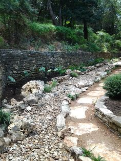 A dry creek bed in Central Austin. This is complete with a variety of plants for sun and shade in and among large and medium size limestone boulders complete with a limestone pathway to the back door.