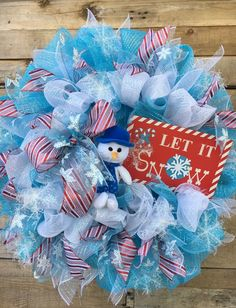 Snowman Wreath, Winter Snowman, Let It Snow Wreath, Winter Door Wreath, Winter Decorative Wreath, Blue Snowman Wreath, Winter Wreath, Christmas Gift  This gorgeous cool winter wreath is large and festive and will add stunning curb appeal to your home!  This beauty is made up of light blue foil deco mesh, white iridescent foil deco mesh, snowflake ribbon, red