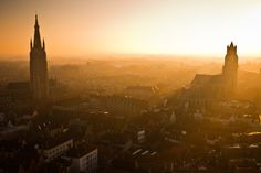 Sunset over Bruges  Photo and caption by Calvin Lee  The Belgian city of Bruges is famous for its stunning medieval architecture. Taken at sunset on top of the Belfort, the city's gothic cathedral spires (the Church of Our Lady on the left, and St. Salvator's Cathedral on the right) and angular roofs are bathed by the warm glow of an ethereal, golden light.
