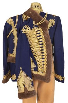 Magnificent British Hussar Officer's Uniform, Circa 1888. The blue wool dolman, the tight inner jacket, is covered in heavy gold lace and cord knots on the front and back and is fully lined. The domed buttons are gilt without regimental designation. The dolman does not have any rank or regimental insignia. The buff wool breeches also have gold lace and cord in Austrian knots. The pelisse, the fur trimmed short jacket.