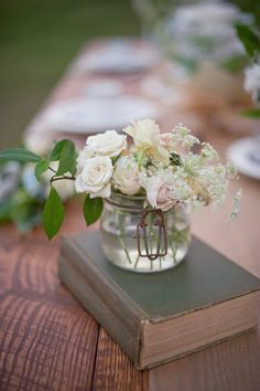 love books propping up a vase of flowers