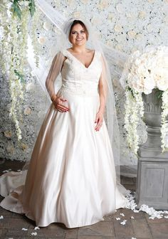 Style 40783 is a beautiful satin dress with a v neck and back fitted to a natural waistline with stunning bead work along the bodice and the back of the dress, the floor length dress has a chapel train and a beautiful ball gown silhouette