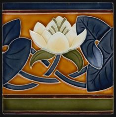 V&B Water Lily Art Nouveau tile Art Nouveau tile decorated with a water Lily in relief. This tile is made by Villeroy & Boch, Mettlach. Tile is in very good condition with only a few light scratches to blue leaves on left side. Nice bright glaze. Clean back with factory name in relief. AN 1375 Germany Date: C 1900