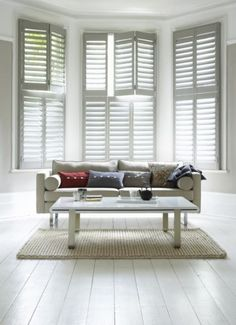 Wood plantation shutters installed on bay window in master bedroom