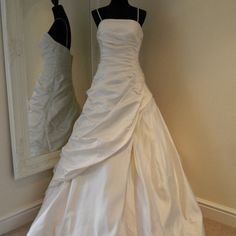 Angelina Faccenda 0801922 is an ivory silk A line gown with removable straps, ruched bodice with stunning crystal embellishments and a layered, side ruched full skirt.Size 14 Brand New with tags *** 30% off RRP ***RRP £1,300.00 £910.00    In stock