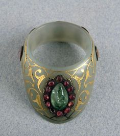 'Zihgir' (archer's ring, worn on the thumb).  Ottoman Empire,16th century.  Jade, gold, rubies.and an emerald._