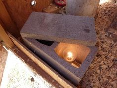 Cinder block heater water warmer - light bulb inside cinder bock covered with a stepping stone water container set on top won't freeze......very clever idea!