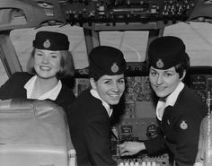 Three air hostesses in the cockpit of an airliner, circa 1965.