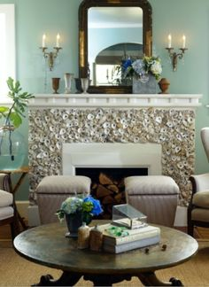 Shell covered fireplace surround...adds natural elements of texture and works well with the sea foam green wall...echoes of the ocean...