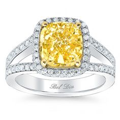 Lavish and marvelous, a Cushion Yellow Diamond Split Shank Engagement Ring is an extremely luxurious piece that utilizes 18kt yellow gold prongs and a cup beneath the halo to enrich the amazing color of the center stone.  0.70 cttw in G color VS diamonds adorn the halo and split shank band of this engagement ring setting.  Such a luxurious piece provides a warming feeling when viewed and emphasizes the joy and happiness that is present in your relationship.  The band can be crafted from 14kt…