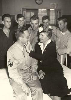 Helen touches the face of a wounded soldier at a hospital in North Carolina, 1945