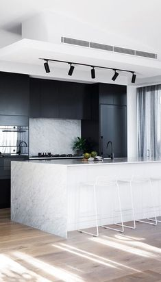 Best Interior Design Ideas : Mixing of Modern and Minimalist Style cool modern kitchen decor idea // track lighting for the ktichen // black stainless appliances // black cabinets // marble wrapped island // minimal modern white stools High End Kitchens, Black Kitchens, Kitchen Black, Quirky Kitchen, Diy Kitchens, Stylish Kitchen, Modern Kitchen Design, Interior Design Kitchen, Kitchen Decor