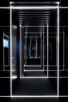 In contrast to the brightly and naturally lit offices, an ominous black corridor is illuminated by harsh strip lighting arranged to create a gridded pattern.