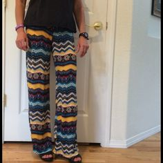 """Palazzo Pants New 🎉Host Pick🎉 Wear these stylish soft, stretchy, comfy palazzo pants everywhere! Pretty black, turquoise, beige, gold and Fuschia pattern. 95% rayon; 5% spandex. Waist 23 -29"""". Sits at natural waist. Hip 35-42"""". Inseam 30"""". New. Never worn. Total Trendsetter Host Pick by @janet0103 😍 😘 Pants Ankle & Cropped"""