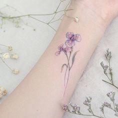 Iris flower tattoo on the inner forearm.