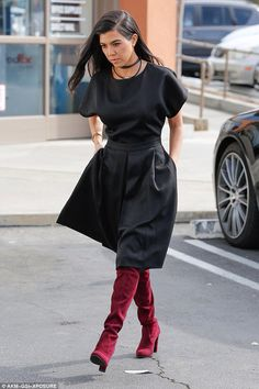 Kourtney, on the other hand, was simply chic in her black short-sleeved frock that had retro written all over it. The dress fit Kourtney loosely on top and was cinched in at the waist before flaring out to the tops of her red suede boots. Kourtney let her raven-black hair hang loose and she swept it away as the sisters emerged from the casual eatery.