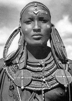 Africa | Maasai woman in tradition earrings (each weighing over a pound) signifying that she's married. Kenya.  | Scanned from a 1954 National Geographic.