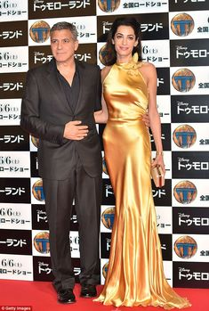 All in the details: Amal was carrying a matching gold handbag as she cosied up to her man...