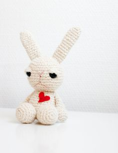 Valentines day bunny crocheted white bunny with a red heart. Cute amigurumi soft toy sculpture. why does he look so angry.