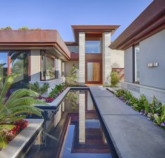 Entry reflecting pool echoing stacked travertine stone columns, entry pivot door of single slab of suar rosewood, and copper fascias.  Architecture and Interior Design by Matrix Design Studio.