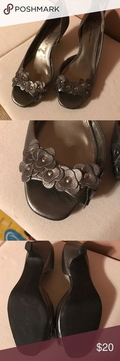 Pretty Pewter short heels with flower detail I don't know if I should call these silver or pewter..... they're more of a pewter color to me. They have just enough heel to be dressy yet comfortable. Really pretty flower detailing on the open toe with silver beads. I wore these once, to my sons wedding. They're in practically new condition 😁 Bandolino Shoes Heels