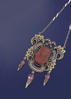 An Art Nouveau silver and enamel pendent necklace  The openwork panel with pliqué a jour enamel lotus flower decoration surrounding an imitation jasper pharaoh head, suspending three enamelled flowerbud drops, to oval-link backchain with white and purple enamel candy-twist bar intervals, circa 1900