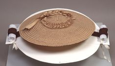 Woman's chip hat ca. 1857–1860; Media: Wood, Silk, And Silk Ribbon; Dimensions: 15 1/2 x 13 7/8 in. England Flat round bergere style hat. 18th c. style, probably revival from the mid -19th c. Trimmed with finely worked thin wood flowers, feathers(broken) and spiral trim. Black silk ribbons(may not be original). Silk lining in crown only. de Young Fine Arts Museums of San Francisco