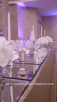 Stunning top table, Sarah wanted to achieve light and a classic look, with square mirrored plates and the brides own vases we added simple hydrangea heads to achieve this classic simple look. ( Rowton Hall Hotel) www.weddingflowersbylaura .com