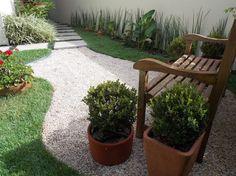 Jardim com primavera e piso de pedriscos.