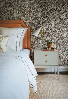 The guest bedroom is cloaked in an Abre de Matisse wallpaper from Quadrille and accented by a natural-fiber rug, Chelsea Editions night table, and modern cone sconce from Circa Lighting   archdigest.com
