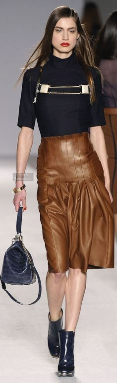 Brown veggie leather pleated skirt paired with black turtleneck top with metal embellishment and ankle boots.. DIY the look yourself: http://mjtrends.com/pins.php?name=brown-veggie-leather-for-skirt_3
