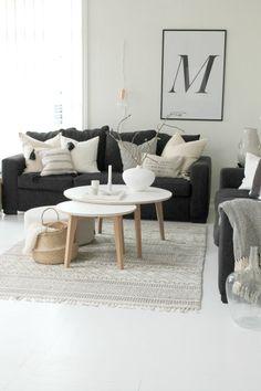 un salon décoré dans le style scandinave : un canapé noir, des murs blancs et un tapis pour réchauffer la pièce.