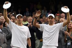 Bob and Mike Bryan hold up the runner-up trophies for the Gentlemen's Doubles Championship on Centre Court - Florian Eisele/AELTC
