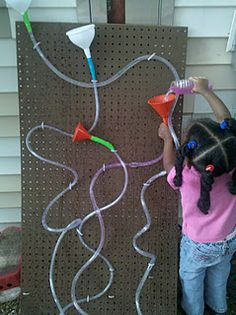 tube and funnel peg board: use a zip tie to fasten the tubes topped with funnels to a peg board. Add a low tub at the base for the water to drain into. Add colored water      They are totally engaged while learning about the effects of gravity on water, flow, measurement, and developing fine motor coordination. Cool, huh?