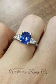 This impressive engagement ring is set with a central emerald cut blue sapphire with baguette and round diamonds  either side of the band. The ring has a millegrain edge around the settings to give the ring a vintage feel. This is an Art Deco style ring and is made in platinum. #bluesapphirering #bluesapphireengagementring #sapphireengagementring #artdecoengagementring #baguettediamondring
