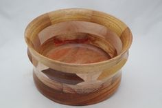 The Exotic Woods Bowl has 19 pcs of exotic woods: Bubinga (Africa) light red with dark streaks,Canarywood (S America) yellow with red hues, Ebony (Southeast Asia) med brown, Hawaiian Sweet Gum (Hawaii) Padauk (Africa) red-orange with dark streaks; Yellowheart( C&S America) yellow,Zebrawood (West Africa) creamy tan with dark streaks, domestic woods: Walnut (USA) med. brown (1 pc), White Maple (USA) light tan (6pcs). It has a multi-layer hand applied acrylic finish. # 642 0752