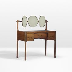 Lot 34: Roberto Gabetti and Aimaro Isola. Custom vanity from Casa Minola, Turin. 1963, padauk, mirrored glass, laminate, brass. 42½ w x 22 d x 49 h in. estimate: $10,000–15,000. Vanity features three drawers and two adjustable ovoid mirrors flanking a fixed circular mirror. Provenance: Casa Minola, Turin | Private Collection