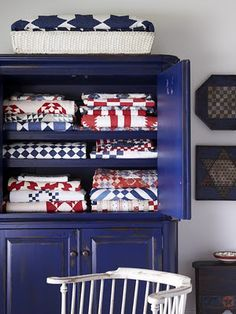 red white and blue quilts in blue armoire