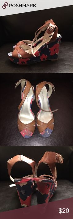 Tommy Hilfiger Floral Wedges Size 7. 1 inch tall platform and 4 inch tall heel. Navy and pink floral patterns. Brown straps. Extremely comfortable and easy to wear. One scratch across the Tommy Hilfiger name on the left heel. Slight lightening of fabric on the toe area of the shoe. Slight darkening of the fabric on the back of the right heel. Both areas of discoloring are barely noticeable. Tommy Hilfiger Shoes Wedges