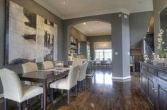 The kitchen, dining room, and living room all flow into one another. No central ceiling chandelier and I love shade of grey Epley selected for the walls. It is called Porpoise by Sherwin Williams.