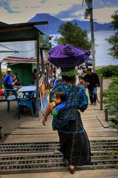 Guatemala - A woman carrying her wares and her child walks to the boat launch on Lago Atitlan