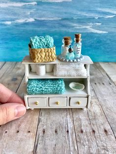This adorable scale shelf will turn any dollhouse bathroom into a beach spa getaway! The shelf is made of wood and has a distressed white finish for a rustic cottage look. The three drawers open and have tiny gold knobs. I hand rolled the toilet paper Miniature Crafts, Miniature Dolls, Miniature Houses, Miniature Furniture, Dollhouse Furniture, Diy Dollhouse, Dollhouse Miniatures, Towel Organization, Bedroom Organization