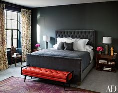 In the master bedroom, an RH bed is grouped with Ralph Lauren Home side tables and a vintage Italian bench from Billy Cotton; the walls are clad in a Clarence House fabric, the curtains are of a Duralee floral, and an antique Moroccan rug is laid atop carpeting by Holland & Sherry.