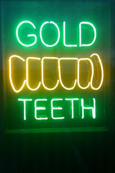 (How you like me now, gold teeth when I smile) Yellow green saying GOLD TEETH