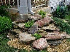Such a creative idea! Stack flat rocks under the gutter downspout for a beautiful dry waterfall landscape idea. Love that they added ground cover plants too! Great for hiding an unsightly corner. :)