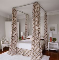 Curtain rods and four-corner drapes secured from the ceiling create a faux canopy bed that adds drama for minimal cost.
