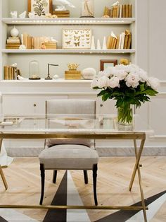 Glass and golden desk, grey chair, decorated shelves, white flowers