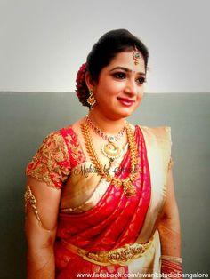 Traditional Southern Indian bride, Bhavya wears bridal silk saree and jewellery for her Reception. Makeup and hairstyle by Swank Studio. Silk sari. Tamil bride. Telugu bride. Kannada bride. Hindu bride. Malayalee bride. Bridal Saree Blouse Design. Indian Bridal Makeup. Indian Bride. Gold Jewellery. Statement Blouse. Armlet. Kamarbandh. Find us at https://www.facebook.com/SwankStudioBangalore